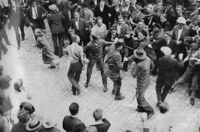 Un policia intenta posar pau entre manifestacions oposades de nazis i comunistes al 1932.